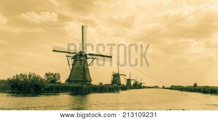 Old-fashioned style image windmills along edge of dyke Kinderdijk district popular tourist destination with it's scenic fields ponds canals and windmills.