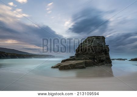 Spectacular sunset on the Spanish beach of the magical monolith with the clouds concentrated in its vertex