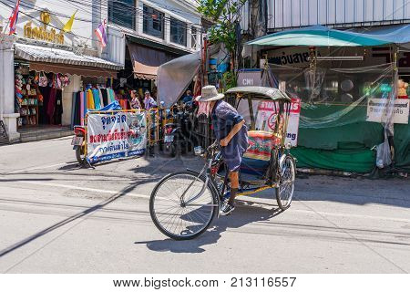 CHIANG MAI THAILAND - JULY 27: Rickshaw driver in the downtown historic centre area of Chiang Mai on July 27 2017 in Chiang Mai