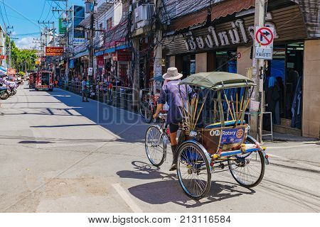 CHIANG MAI THAILAND - JULY 27: Rickshaw driving down a road in the downtown historic centre area of Chiang Mai on July 27 2017 in Chiang Mai