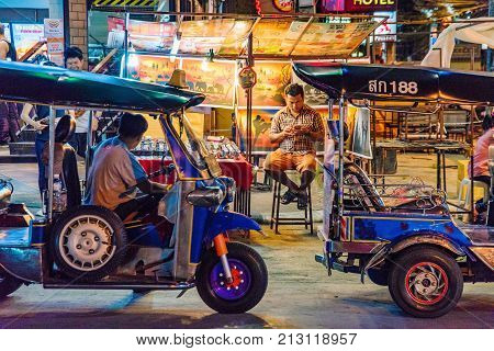 CHIANG MAI THAILAND - JULY 30: Night market street scene of tuk tuks with stalls in the background in the famous Chiang Mai night bazaar on July 30 2017 in Chiang Mai