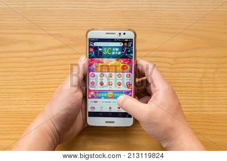 ZhongshanChina-November 112017:man shopping through mobile on JD on Chinese online shopping day on November 11.Nov 11 is the shopping day of China and online shopping is very popular in China.