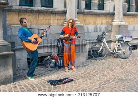 Bruges Belgium - 11 April 2017 - Two happy street musicians perform their music for donation on a street of Bruges Belgium on April 11 2017