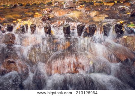 Water stream of river in rainforest overflow through wooden weir and rocks.