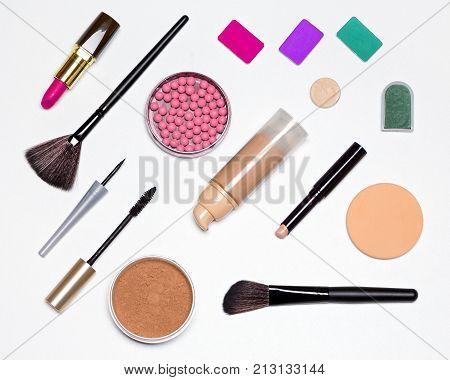 Makeup must haves. Basic contents of cosmetic bag. Concealer stick, foundation, powder, blush, eyeliner, mascara, eyeshadow, lipstick, make-up brushes and sponge