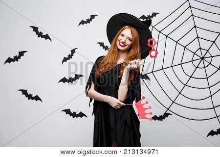 Halloween Concept - Beautiful Girls In Black Witch Dresses Holding Party Props.