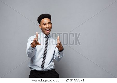 Business Concept - Cheerful Happy Young African American Holding Gun Sign With Fingers Pointing To O