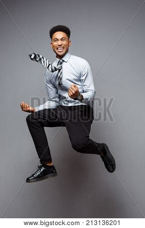 Business Concept - Full Length Portrait Of Successful African American Businessman Happy Jumping In