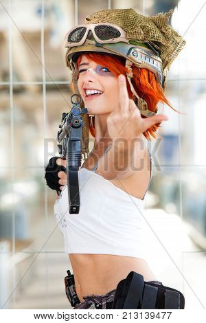 Rude defiant army girl. Military woman with gun. Rude and confident girl. Military woman with gun. A girl, young woman armed military defiantly make a rude gesture.