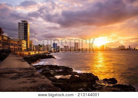 Romantic sunset at the Malecon seawall in Havana with a view of the sea and the waterfront buildings