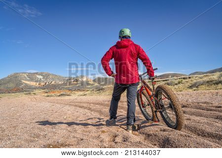 a tired male cyclist with a fat bike contemplating a tough and long ride through deep gravel on Big Hole Wash Trail in Red Mountain Open Space, Colorado