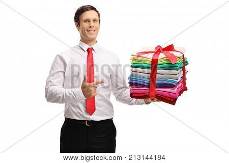 Formally dressed guy holding a stack of ironed and packed clothes wrapped with red ribbon as a present and pointing isolated on white background