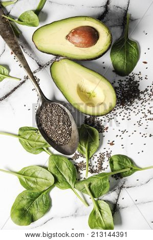 Fresh healthy ingredients for a breakfast on a marble table. Healthy life concept with avocado,chia seeds and spinach leaves
