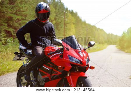 Krasnoyarsk, Russia - August 09, 2017: A Motorcyclist Wearing A Helmet With A Black Visor And Red Sp