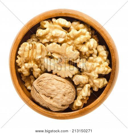 Whole walnut and shelled walnut kernel halves in wooden bowl. Seeds of the common walnut tree Juglans regia. Snack or used in bakery. Isolated macro food photo close up from above on white background.