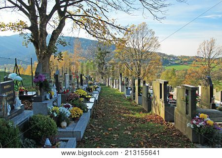 : various decorated graves on the cemetery and some trees in autumn, Prazmo, Czech Republic, November 4, 2017