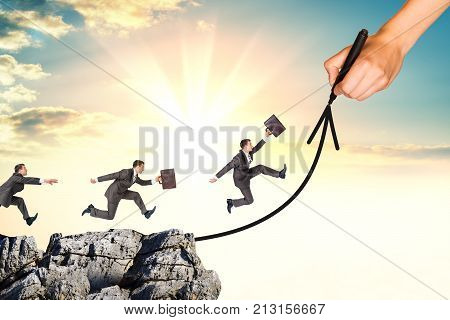 Hand using a pencil draw path like a arrow up. Team businessman running on the way