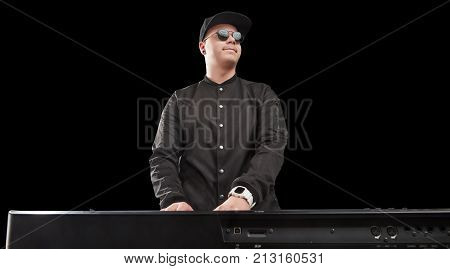 man playing on synthesizer isolated on black background