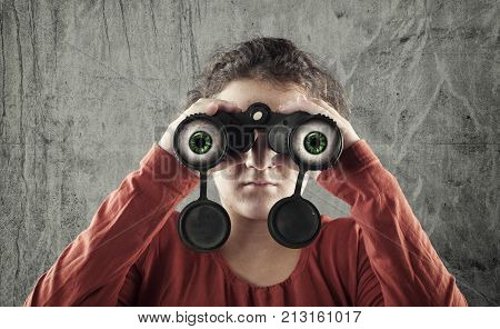 Young girl looking throush a binocular and her eyes reaches out of it .