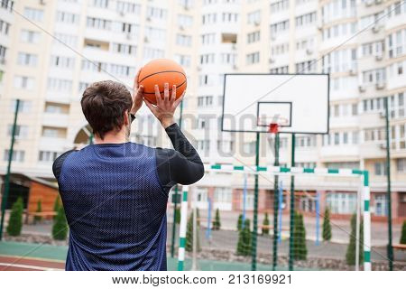 Basketball player in an open autumn stadium, training to throw a ball into the ring. View from the back