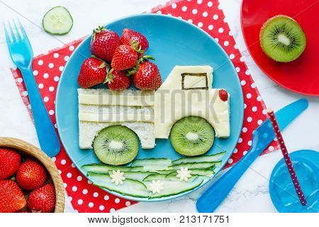 Food art for kids - edible car sandwich with fruit and berries top view