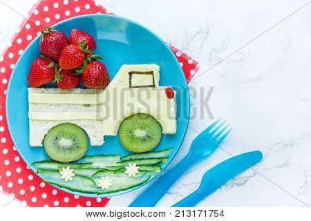 Funny toast in a shape of car sandwich with cheese strawberry and kiwi food for kids idea top view