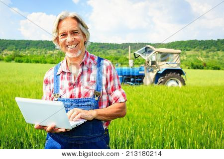 farmer standing in a field with his tractor, selling his produce over the internet