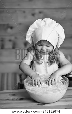 small cute baby boy or child with happy face in white cook uniform with chef hat and apron kneading dough with flour in glass bowl in kitchen on wooden or wood background