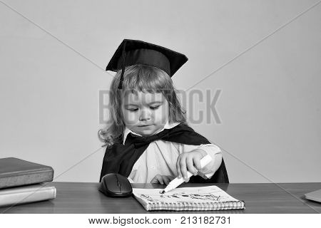 Little boy cute kid student blond in blue shirt black graduation gown and squared cap at school wooden desk drawing in note book by marker near computer mouse and diaries on gray background