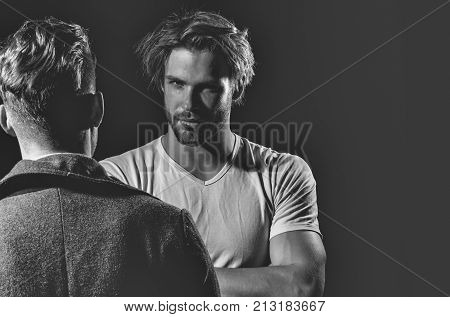 Two handsome men standing with faces opposite on black background. Muscular macho unshaven caucasian in white tshirt with folded arms biceps triceps. Male businessman in dark coat