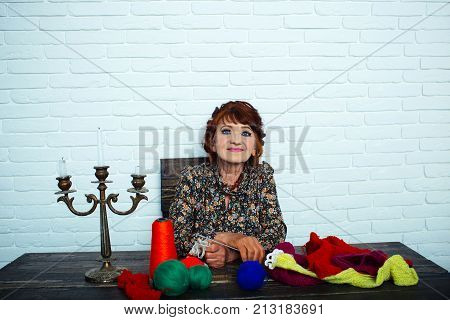 Pension and retirement old age. Needlework and knitting hobby. happy old lady or grandmother with needle and yarn. Granny character at Christmas eve. Old woman knitting socks from colorful thread.