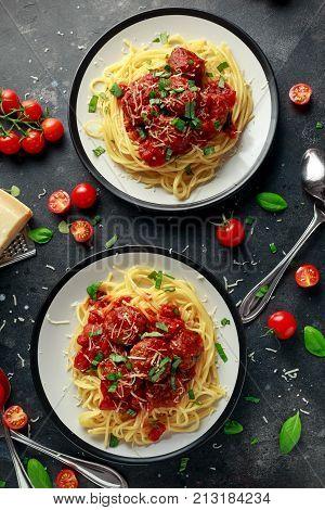 Spaghetti pasta meatballs with tomato sauce, basil, herbs parmesan cheese on dark background.