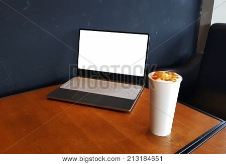 Laptop with coffee cup home office. laptop white screen on sunset. Laptop on table. Laptop on vintage tone. Laptop in cafe. Laptop and smartphone on wood table.
