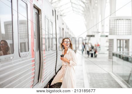 Young and beautiful woman with coffee cup boarding in the train at the modern railway station