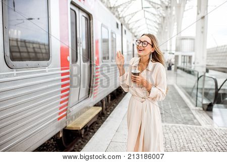 Woman waving with hand saying goodbye near the train at the railway staion