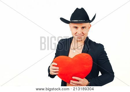 A man is a womanizer. Man of ladies. Man of womanizer in a black suit and hat with a heart in hands on a white background.