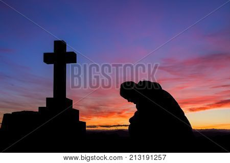 Mand in prayer by a cross at first light of the day.