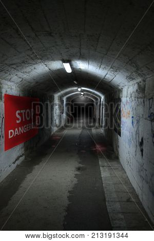 The old dark creepy underground concrete tunnel or corridor is leaving into the darkness. On the wall there is an inscription: the stop is dangerous! Blood on the floor