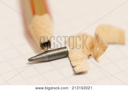 Sharpened Pencil With A Broken Tip Over A Blank Sheet Of Paper