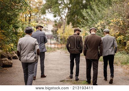 A group of dangerous retro gangsters are walking in the park with their hands in the pockets of their trousers. View from the back.