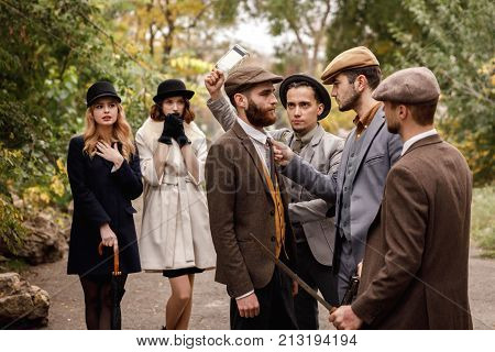Dangerous gangsters are jeered by a big knife and want to hit a bottle on the head with the back of a man with a beard under women, disassembly, intimidation, a retro concept.