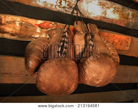 Boxing gloves on the wall. Old, vintage pair of leather mittens hangs on the wood wall. Red colors and soft lights. Gloves of retired boxer and fighter. It hangs on a nail in a barn or rustic house