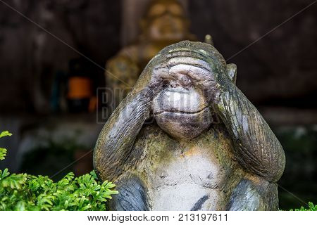 Three monkeyclose up of hand small statues with the concept of see no evil hear no evil and speak no evil.