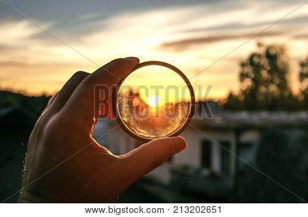 human hand holding photographer dusty uv filter on sunset lights