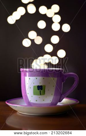 purple cup of coffee with bokeh lighs in background