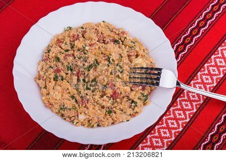 Traditional Bulgarian vegetable dish mish mash with mixed baked peppers tomatoes cheese onion and scrambled eggs.