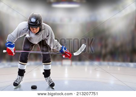 Low angle view of hockey player handling puck on ice with sports arena full of fans in the stands and copy space. Shallow depth of field on background.
