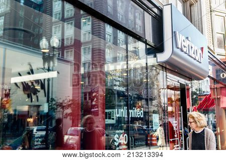 Boston October 28 2017: Woman is passing by a Verizon store and looking inside through the window.
