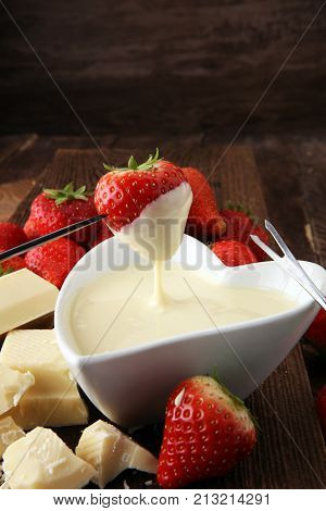 Chocolate fondue melted with fresh strawberries and white chocolate pieces.