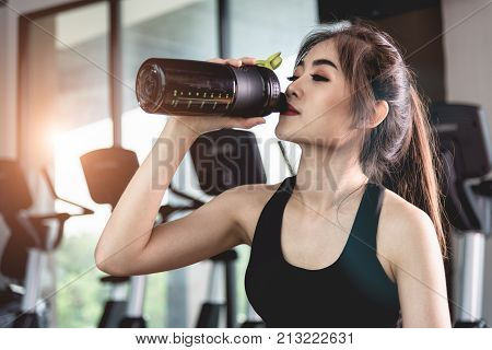 Sports Young Woman With Protein Cocktail In Shaker Sits In Gym